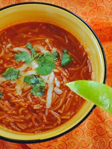 sopa de fideo in a yellow bowl on an orange table cloth