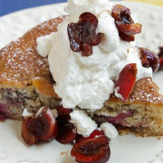 slice of cherry almond cake topped with whipped cream and sliced cherries on a white plate