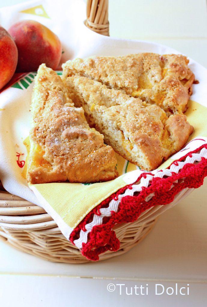 three peach scones in a basket on a napkin with fresh peaches