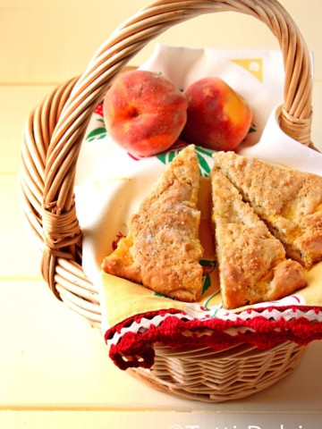 3 peach scones with 2 peaches on napkins in a basket