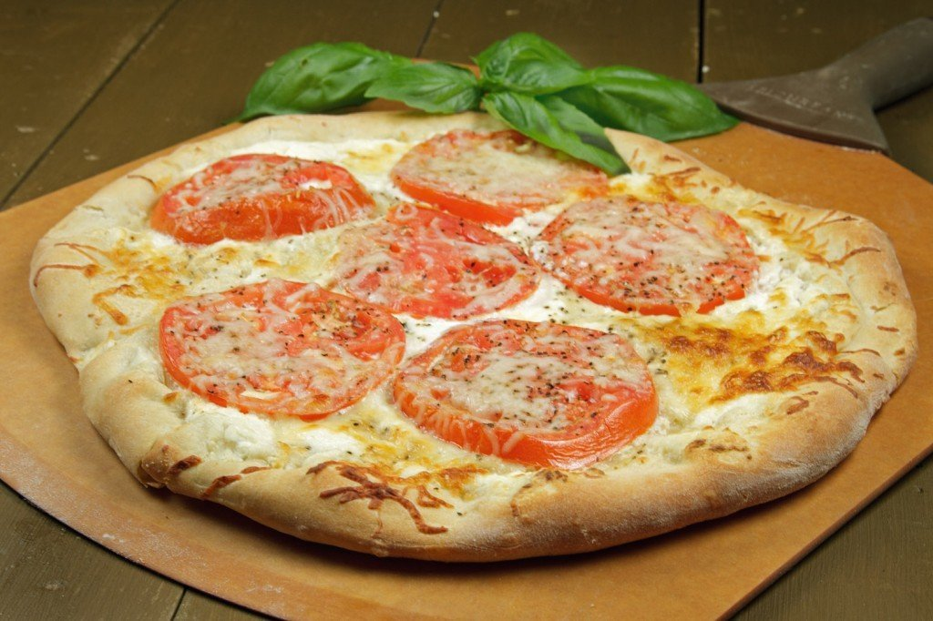 tomato ricotta pizza with a sprig of basil on a pizza peel