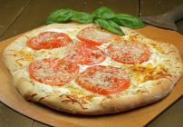 ricotta tomato pizza with a sprig on basil on a pizza peel