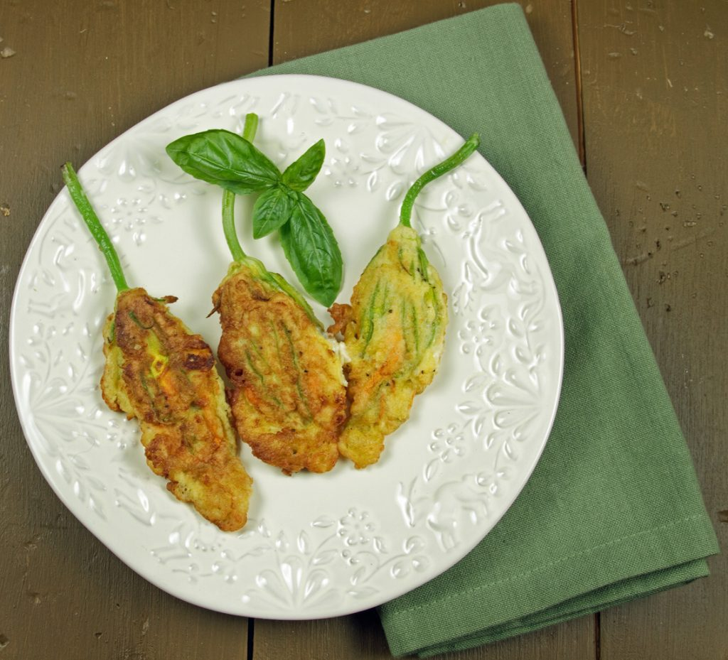 3 fried zucchini blossoms on a white plate on top of a green napkin