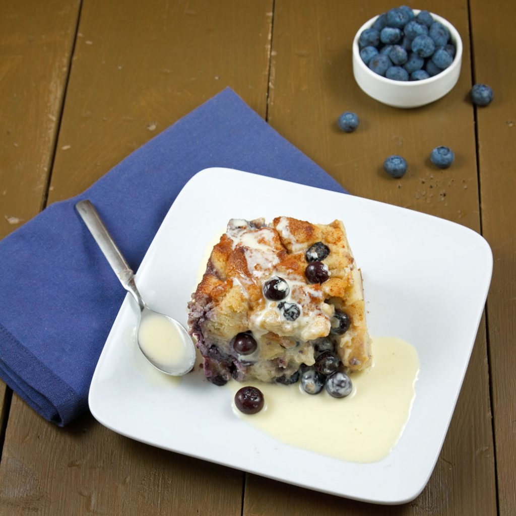 blueberry bread pudding on a square white plate with a vanilla sauce and spoon on a blue napkin on a dark brown table