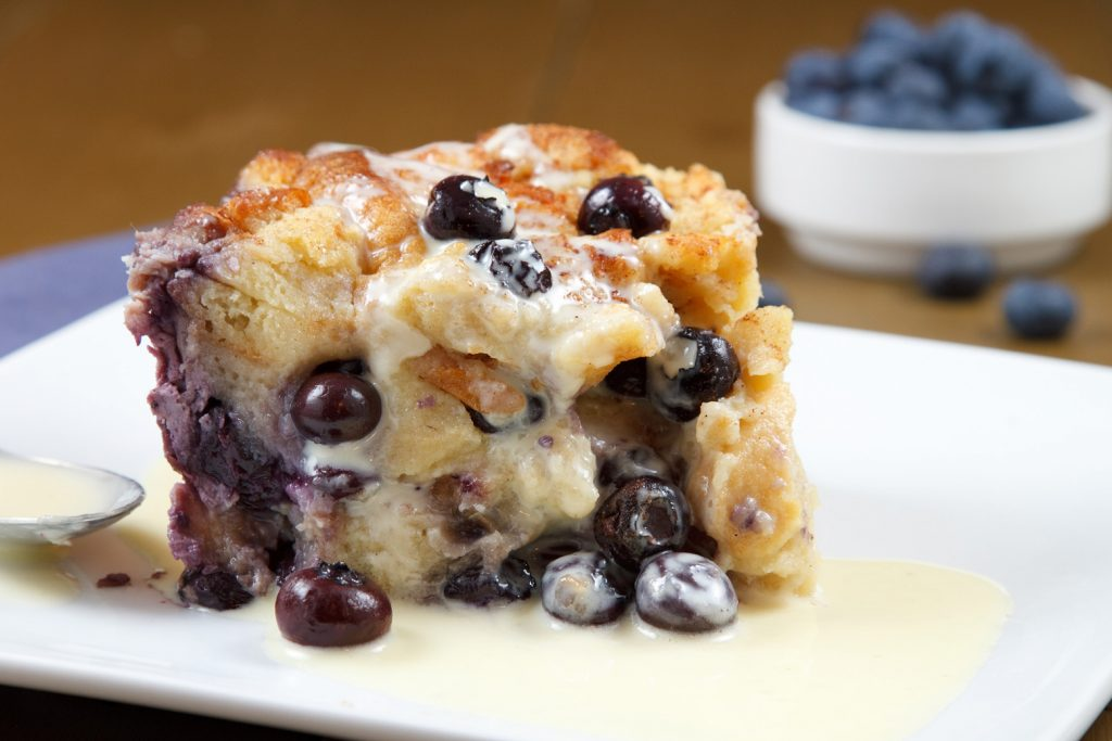 close up view of blueberry bread pudding on a white plate with a creme anglaise sauce