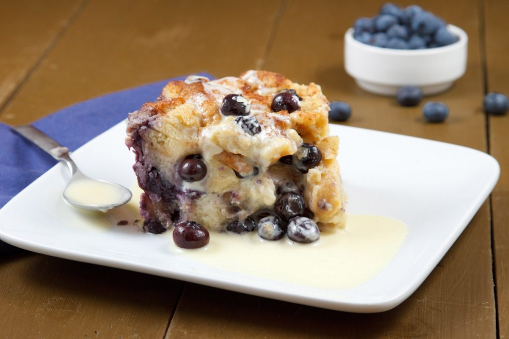 Front view of blueberry bread pudding sitting on a white plate with a spoon and creme anglaise . sitting on a blue napkin on a brown table with blueberries in the background