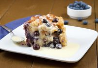 A piece of blueberry bread pudding with creme Anglaise on a white plate