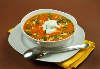 roasted red pepper soup in a white bowl on a white plate with a spoon