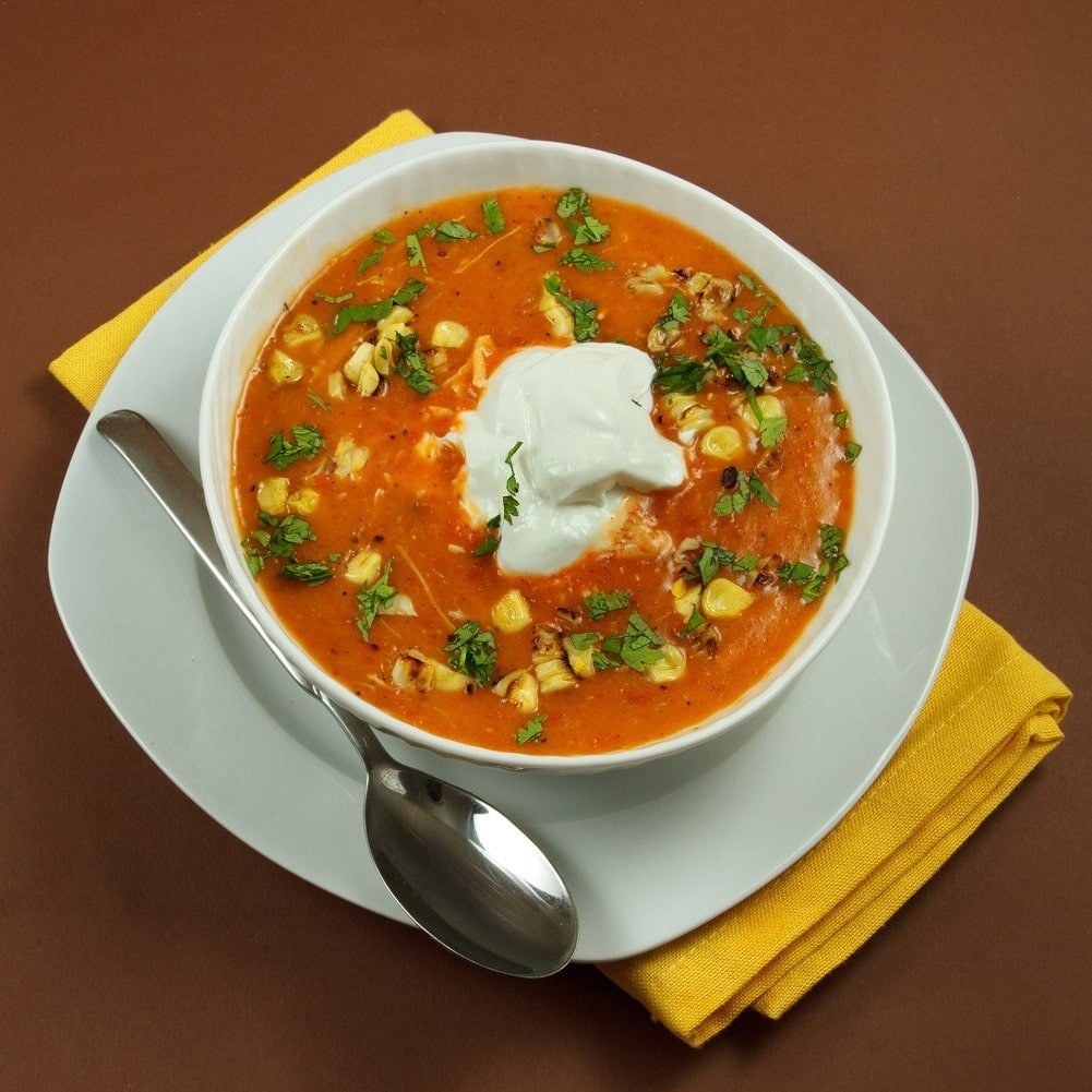 white bowl of roasted red pepper soup with corn and a dollop of sour cream on top sitting on a white plate with a spoon sitting on a yellow napkin