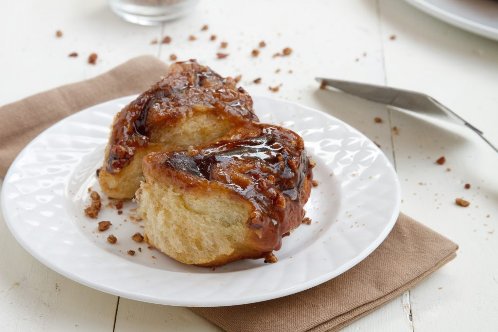 sticky buns on a white plate on top of a light brown napkin sitting on a white table