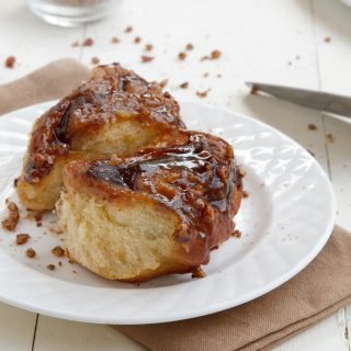 2 pecan sticky buns on a white plate