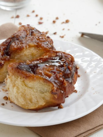 2 pecan sticky buns on a white plate