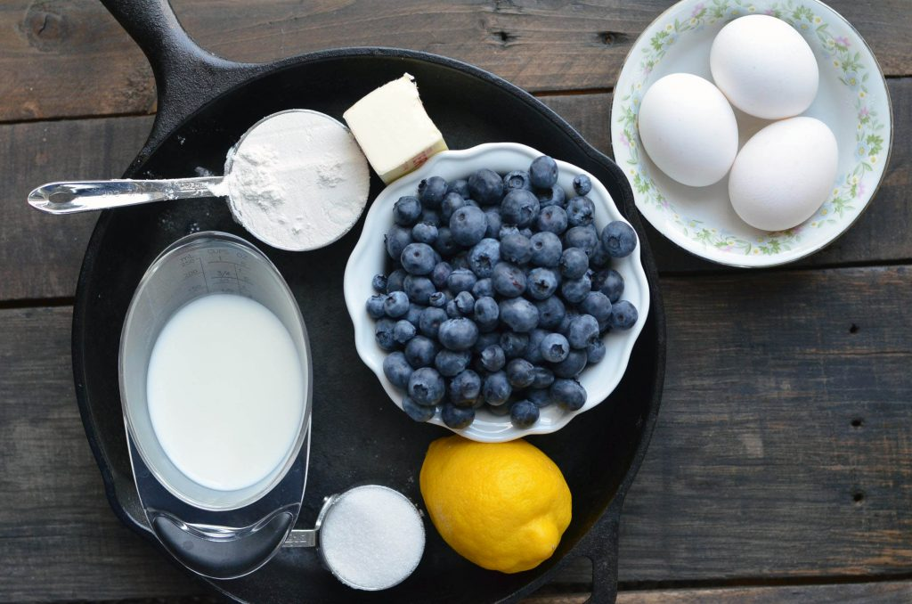 ingredients to make a blueberry lemon dutch baby on a cast iron pan sitting on a wooden table