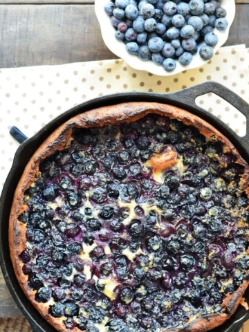 overhead view of blueberry dutch baby in a cast iron pan