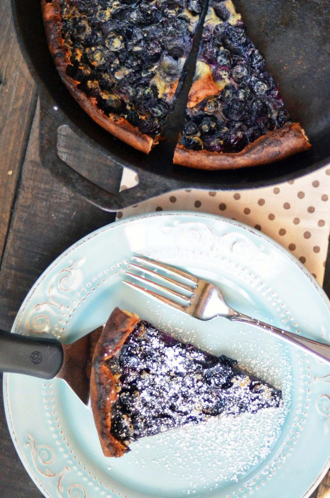 slices of a blueberry lemon dutch baby in a cast iron pan