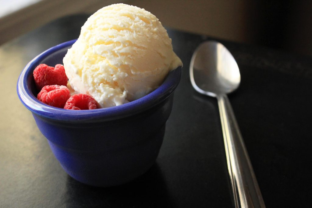 Lemon Curd Mascarpone Ice Cream in a blue bowl with raspberries and a spoon sitting next to the bowl