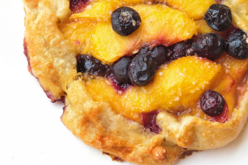 partial view of a blueberry peach crostata on a white plate