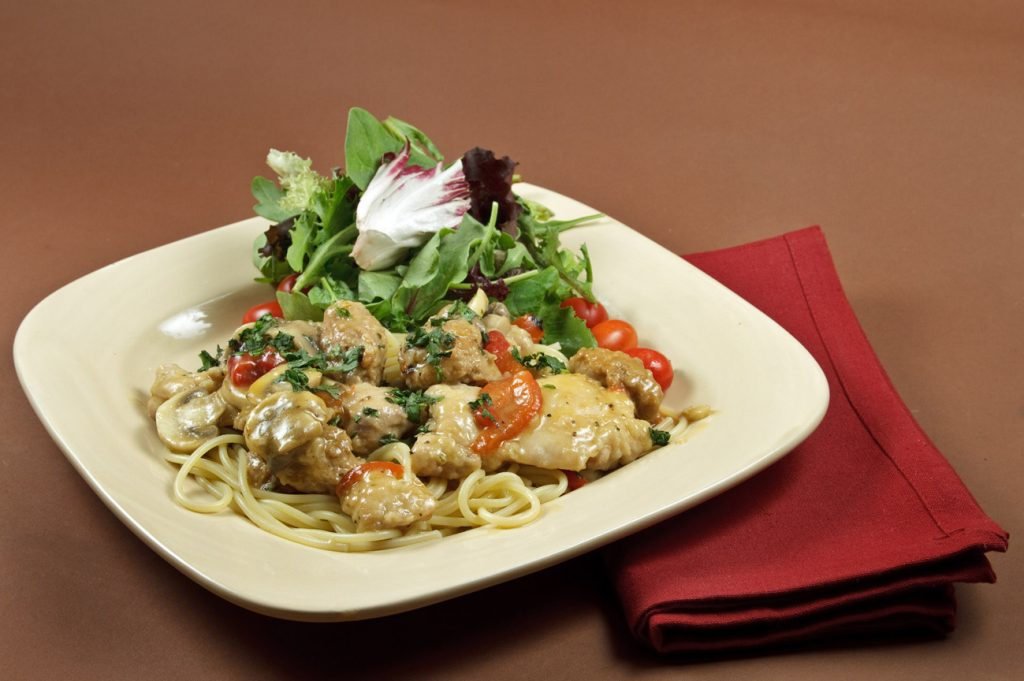 Tuscan Chicken and Sausage saute dish with spaghetti on a cream colored square plate with salad green garnish and a red napkin on a brown background