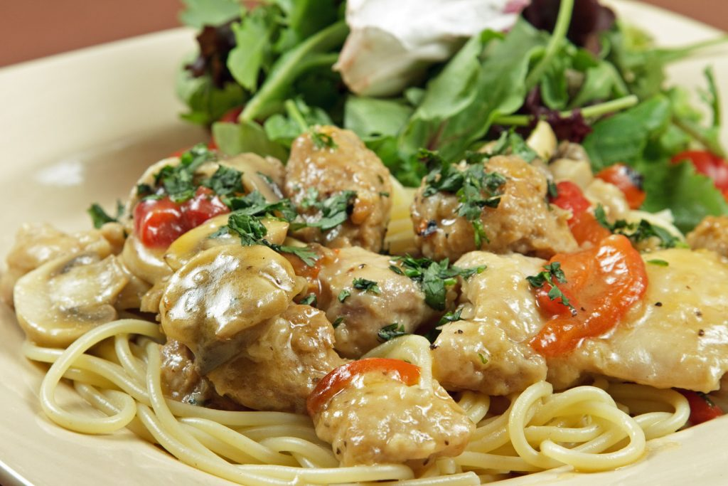 Tuscan Chicken and Sausage saute dish with spaghetti on a cream colored square plate with salad green garnish
