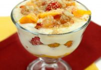 glass dish of peach tiramisu with a lady finger sticking out