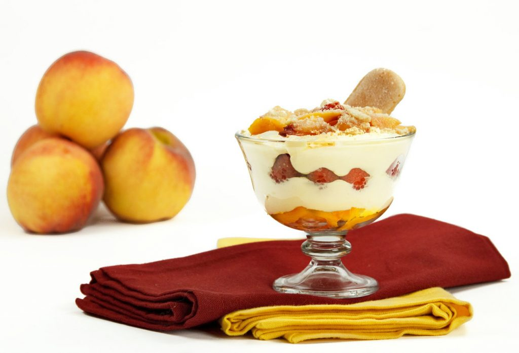 peach tiramisu with raspberries in a glass dish on a red and yellow napkin