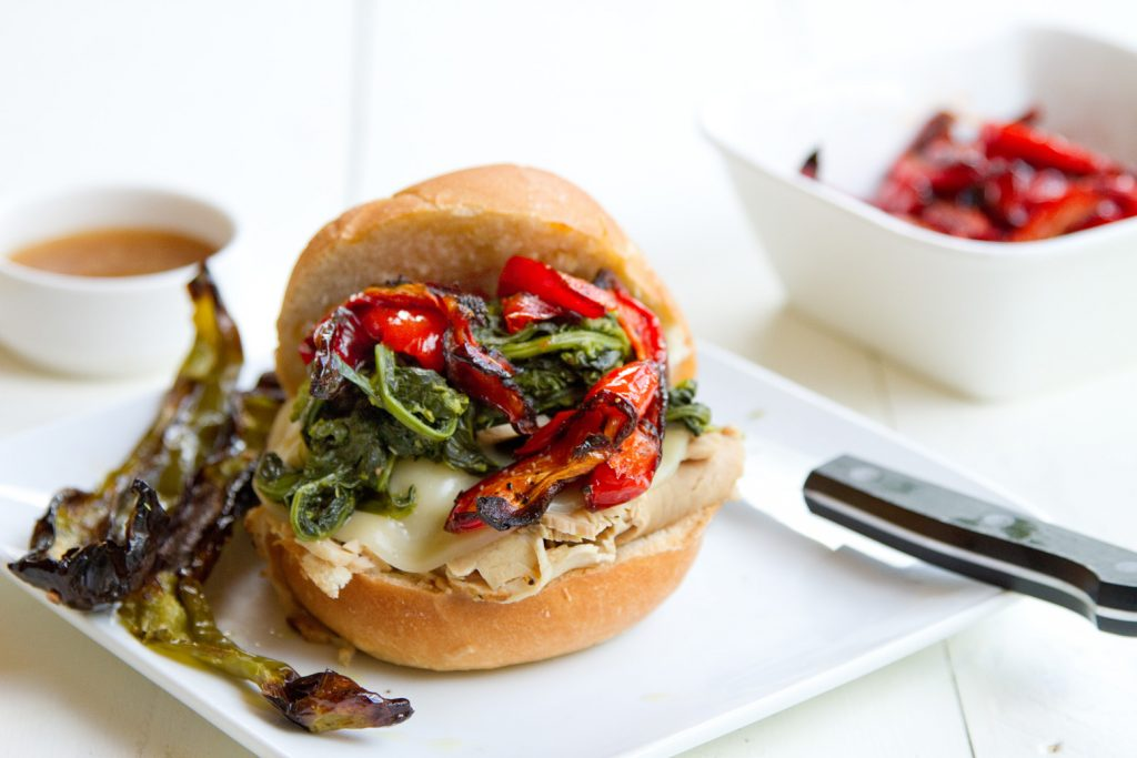 roast pork sandwich with provolone cheese, roasted red peppers and broccoli rabe sitting on a white plate on a white table with a steak knife on the plate and a bowl of roasted red peppers and ramekin of au jus in the background