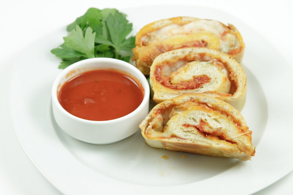 slices of pizza roll ups on a white plate with pizza sauce in a small bowl