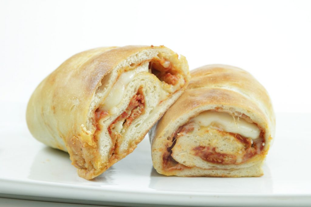 side view of pizza roll ups  showing the filling on a white plate