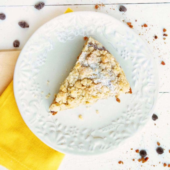 overhead view of a slice of banana crumb cake on a white plate with a yellow napkin on a white table