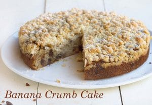 banana crumb cake with a slice missing on a white plate on a white table