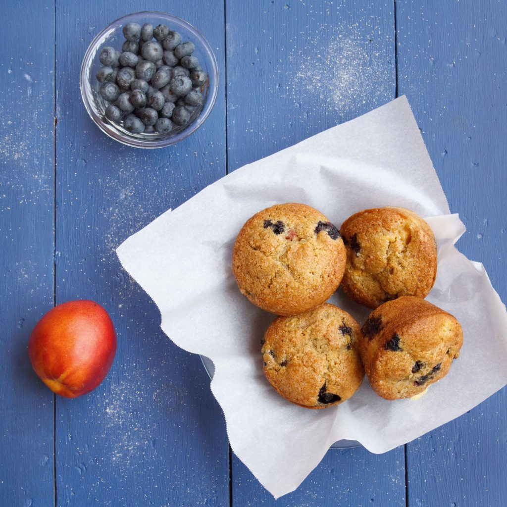 nectarine blueberry muffins sitting on a white paper with a nectarine and glass bowl of blueberries all sitting on a blue table