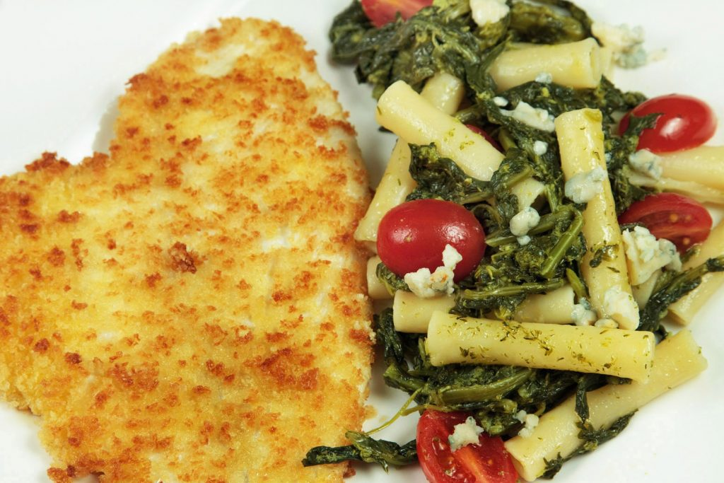 Panko breaded flounder with broccoli rabe pasta on a white plate