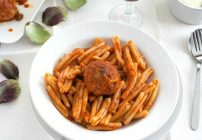 white bowl with pasta and a stuffed artichoke in red sauce