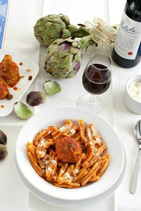 white bowl with pasta and a stuffed artichoke in red sauce with other ingredients around it