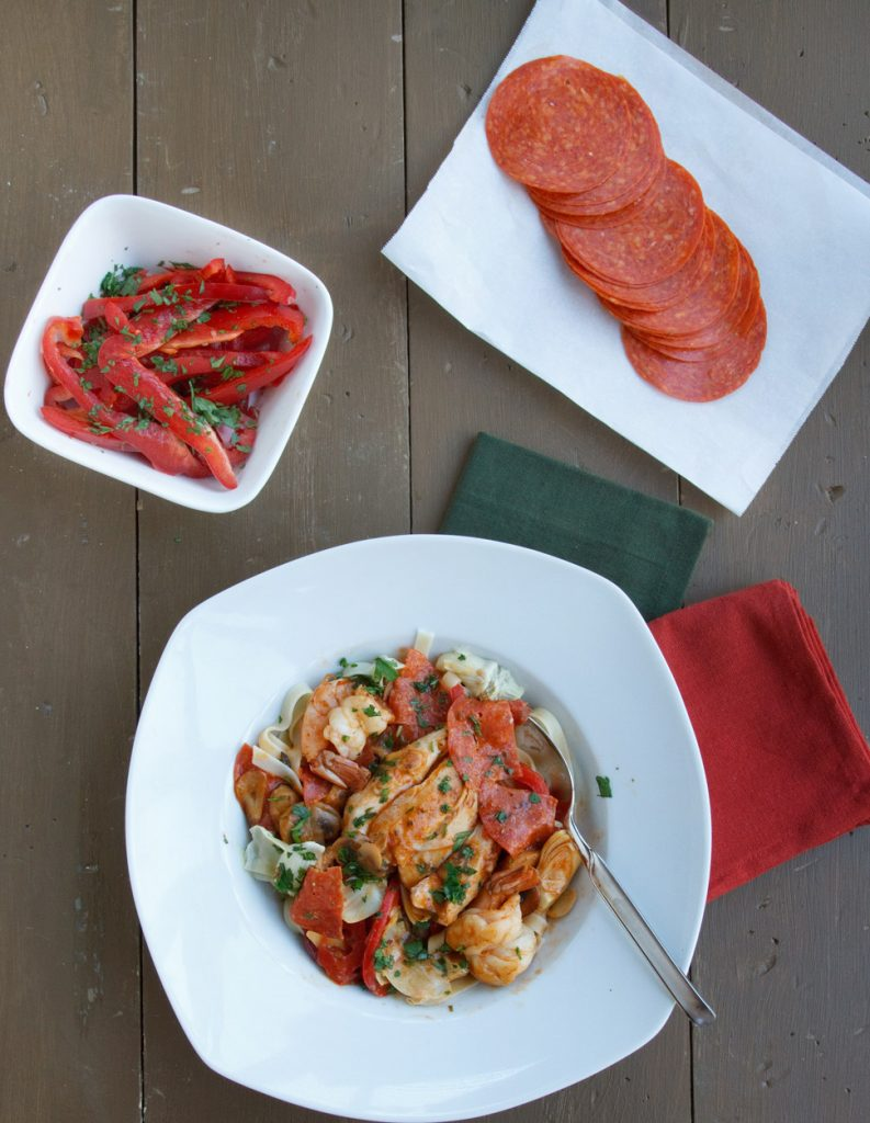chicken and shrimp pepperoni in a white bowl on a brown table with a dark green napkin and red napkin next to a bowl of red peppers and a plate of sliced pepperoni