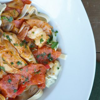 chicken and shrimp pepperoni in a white bowl on a brown table with a dark green napkin