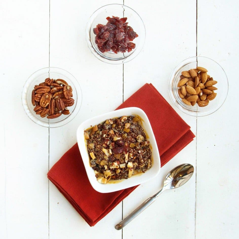 white bowl of dulce de Leche quinoa on top of a red napkin with bowls of fruit and nuts around it