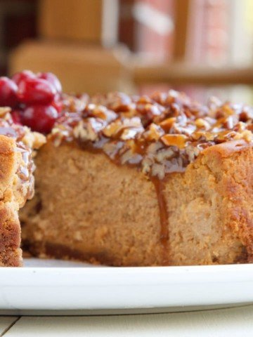 A close up of pumpkin praline cheesecake with a slice cut out on a white plate