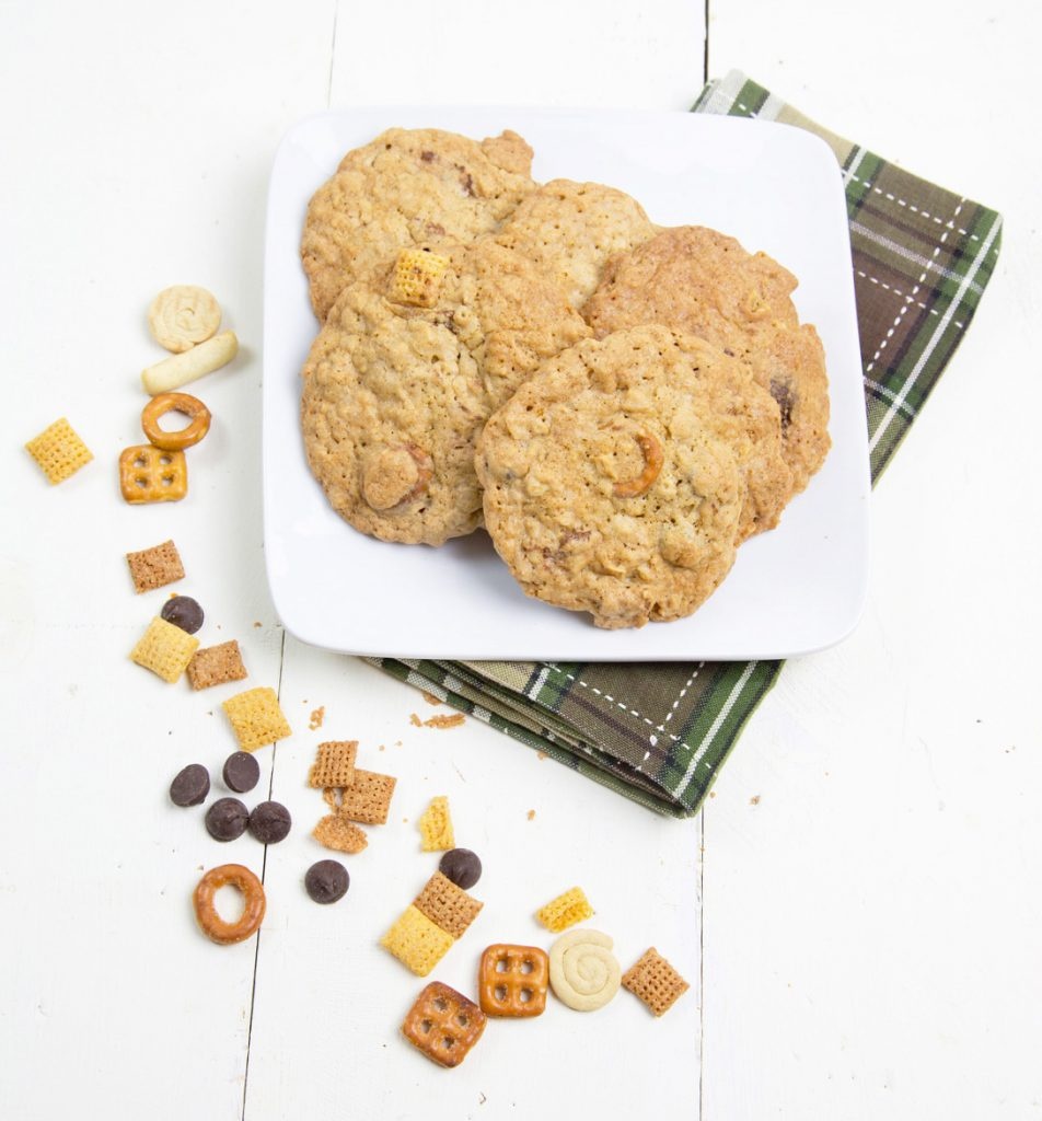 chex mix cookies on a square white plate with a green checked napkin under the plate and chex mix around the plate