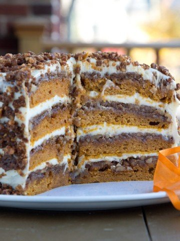 Pumpkin Crunch cake on a white platter with slices taken out showing the inside of the cake