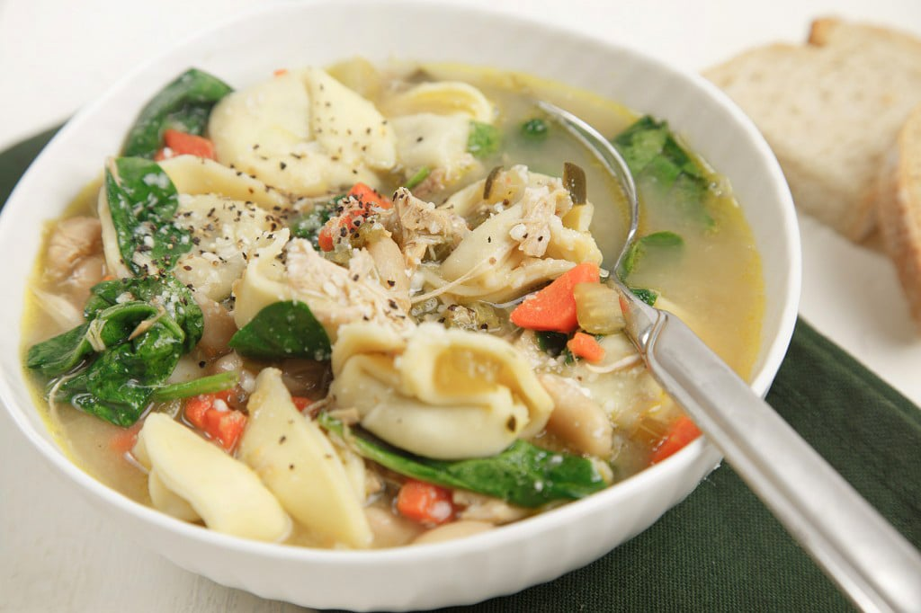 white bowl with chicken tortellini soup with a spoon in the bowl sitting on a green napkin