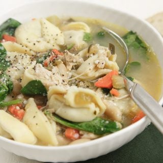 white bowl with sausage and tortellini soup with a spoon