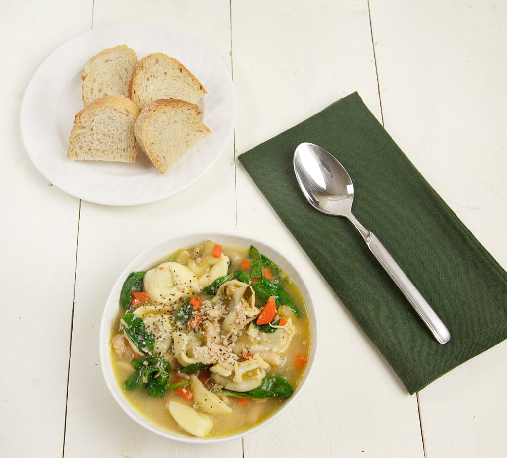 white bowlful of chicken tortellini soup sitting on a white table with a plate of sliced bread and a spoon sitting on a green napkin