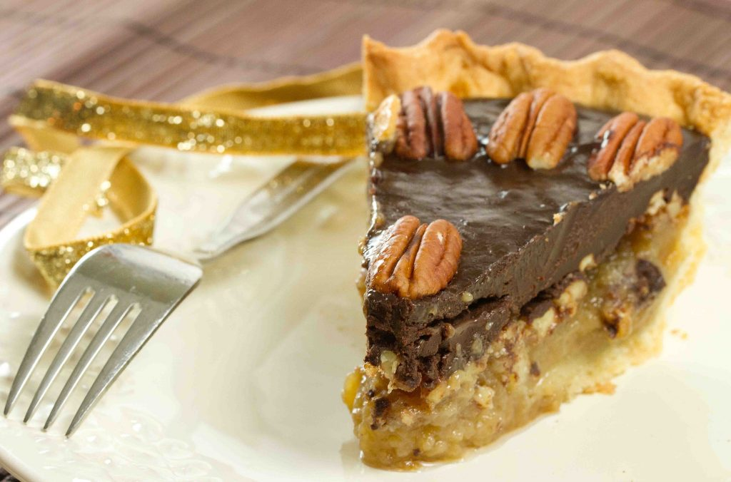 slice of chocolate topped pecan pie on a white plate