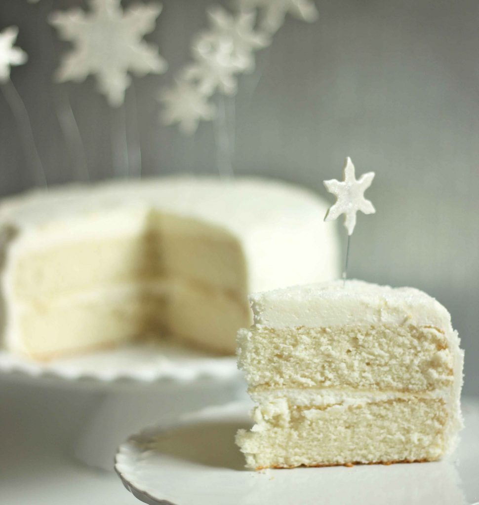 slice of white christmas cake on a white plate with the rest of the cake in the background