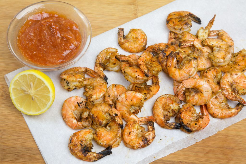 grilled u-peel shrimp on white paper with a half a lemon and bowl of cocktail sauce