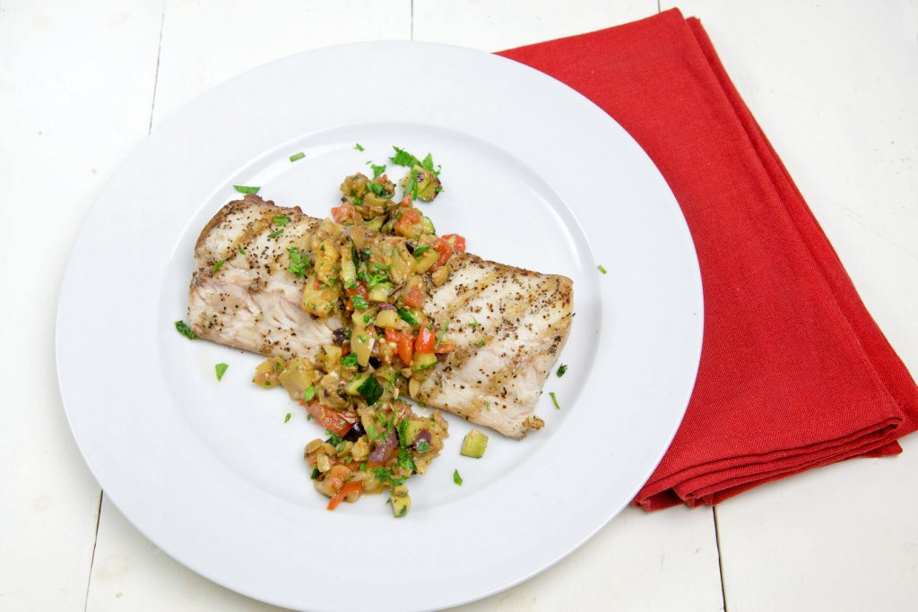 grilled mahi-mahi with a caponata topping on a white plate with a red napkin