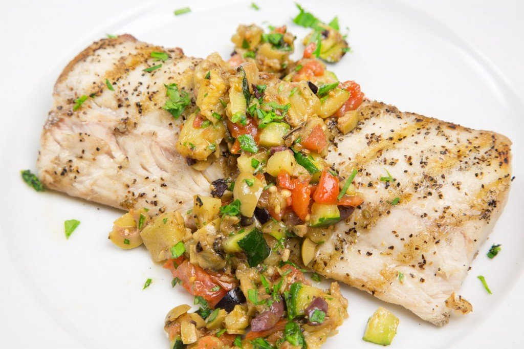 grilled mahi mahi with caponata topping on a white plate