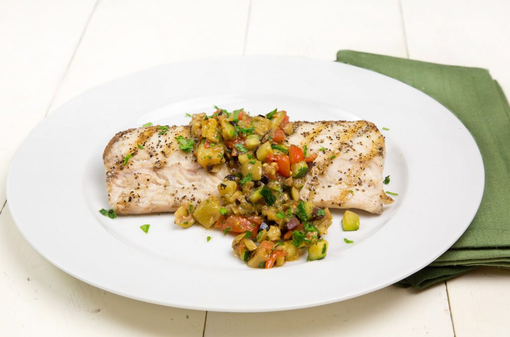 grilled mahi-mahi with a caponata topping on a white plate with a green napkin on a white table