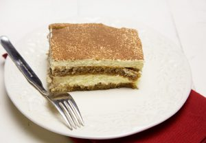 a slice of tiramisu with a dusting of cocoa sitting on a white plate with a fork on the plate